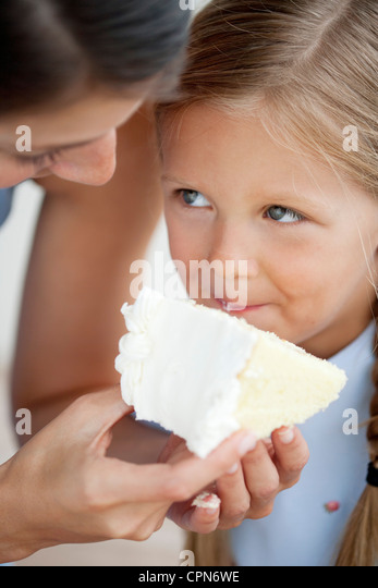 Mother feeding little girl cake - Stock-Bilder