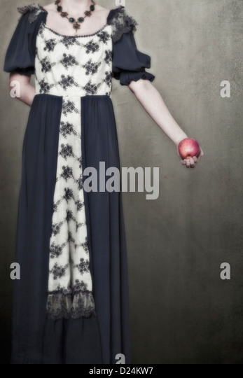 a woman in a period dress is holding an apple in her hand - Stock Image