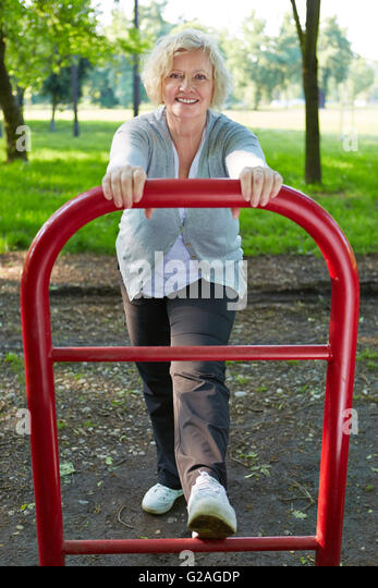 Active senior woman exercising on a keep fit trail in summer - Stock Image