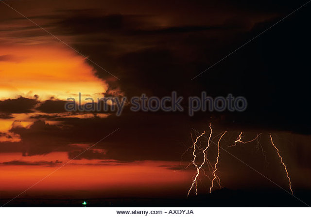 thunderstorm near Casa Grande Arizona in a farm field at sunset dusk with orange sky. This is a marginal lightning - Stock Image