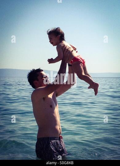 Father and daughter having fun on beach - Stock Image