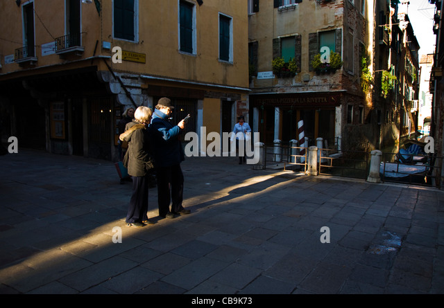 Tourists looking at city map guide in early morning light - Stock Image