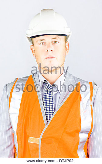 A serious responsible young man in the high visibility orange jacket and hard hat, representing a health and safety - Stock Image