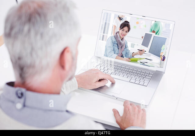 Composite image of closeup rear view of a grey haired man using laptop at desk - Stock Image