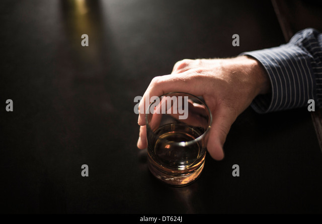 Close up of solitary man with drink in bar - Stock-Bilder