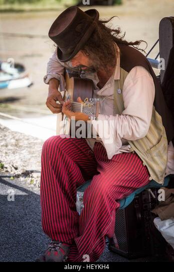 a musician busker playing acoustic guitar at Padstow Harbour in  Cornwall, UK - Stock Image