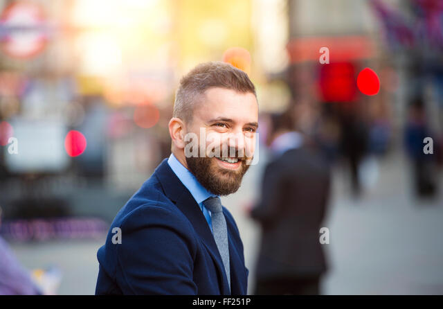 Hipster manager in the crowded street of London, Piccadilly Circus - Stock Image