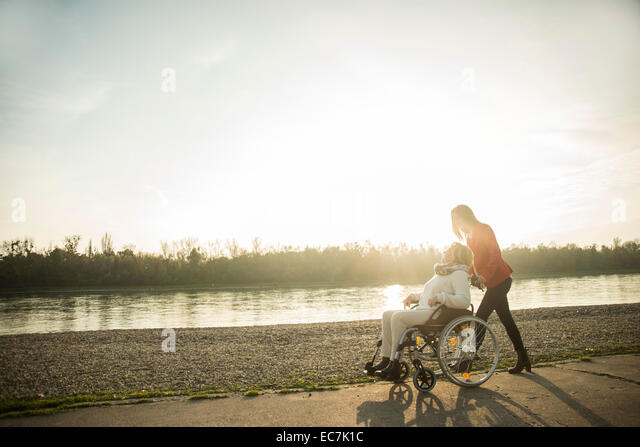 Adult granddaughter assisting her grandmother sitting in wheelchair - Stock-Bilder