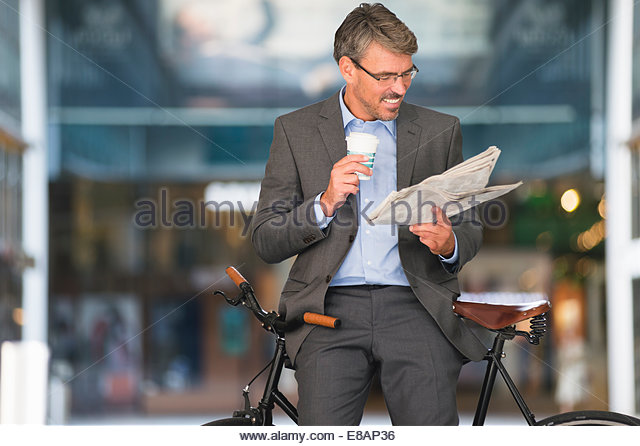 Mature businessman reading newspaper and drinking takeaway coffee - Stock Image