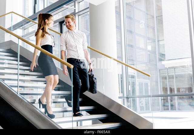 Business colleagues talking on stairs and flirting - Stock Image
