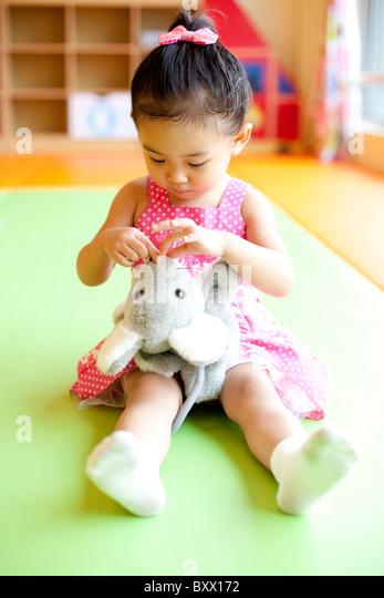 Girl Playing With Stuffed Animal - Stock Image