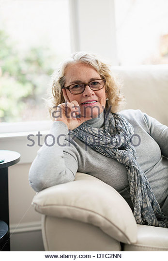 Portrait of happy senior woman sitting on sofa - Stock Image
