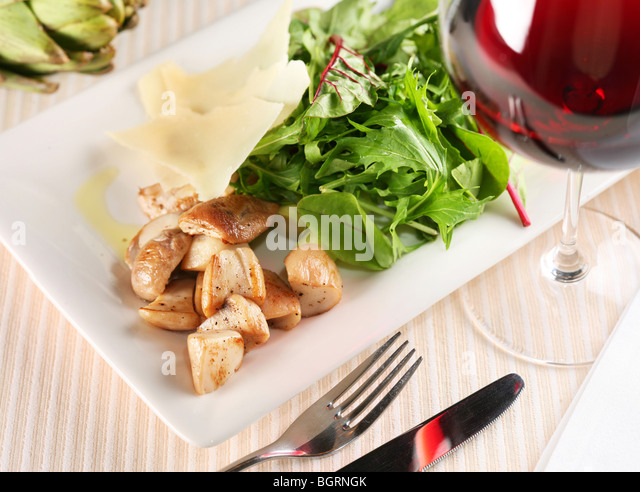 Salad with porcini mushrooms and arugula on a white plate - Stock Image