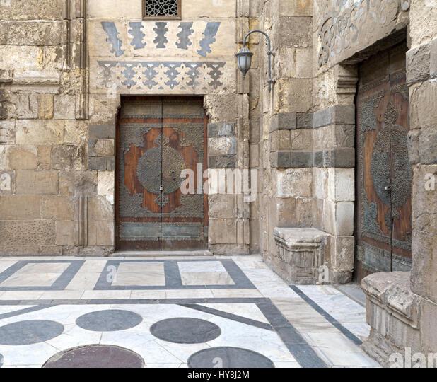 Two perpendicular aged doors at the main courtyard of Al-Sultan Al-Zahir Barquq mosque. Al-Moez Street, Old Cairo, - Stock Image