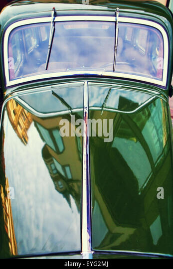 Latvia. Riga. Reflection of the old town on the hood and windshield of a retro car - Stock Image