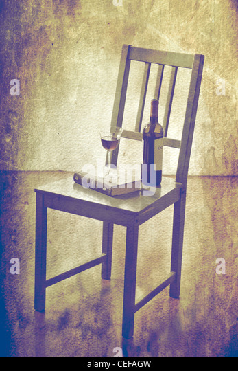 Wine bottle and wine glass with a book on an old wooden chair - Stock Image