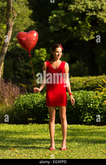 Woman with red heart shape balloon standing in park - Stock Image