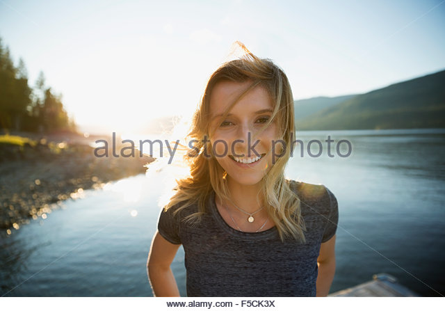 Portrait smiling young woman at sunny lakeside - Stock Image