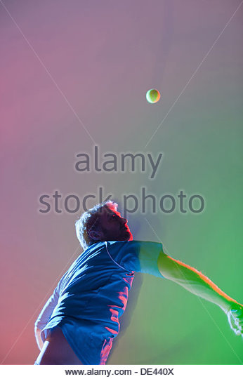 Tennis player swinging racket - Stock Image
