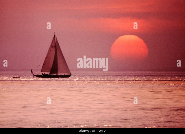 LARGE SUN AT SUNSET WITH YACHT SAILING PAST ON SEA - Stock Image