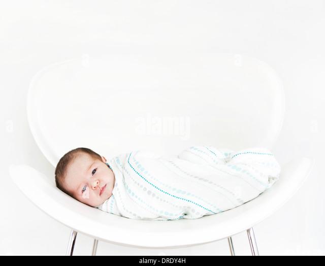Swaddled baby on white chair - Stock-Bilder