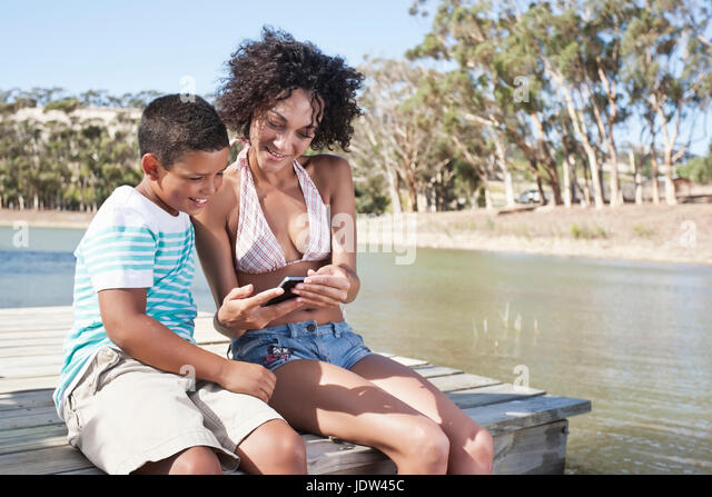 Woman and boy sitting on pier looking at photos on camera - Stock-Bilder