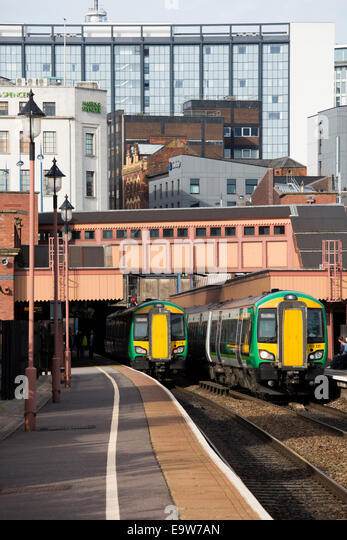 Railway trains passing through Moor Street Station with the backdrop of Birmingham behind - Stock Image