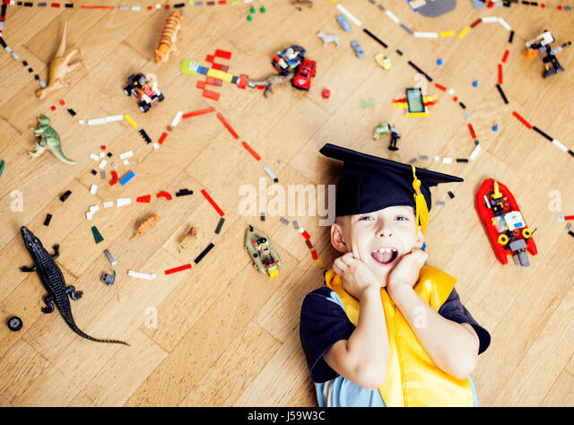 little cute preschooler boy among toys lego at home education in graduate hat smiling posing emotional, lifestyle - Stock Image