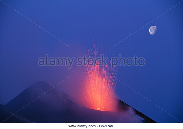 The moon hovers a safe distance from exploding magma, Stromboli, Italy - Stock Image