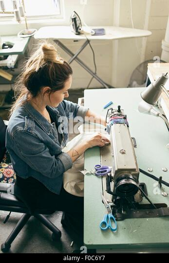 Female seamstress using sewing machine in fashion studio - Stock Image