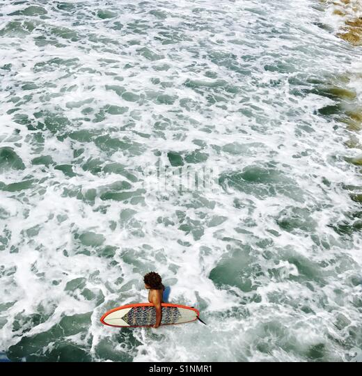 A male surfer walks out to surf. Manhattan Beach, California USA. - Stock Image