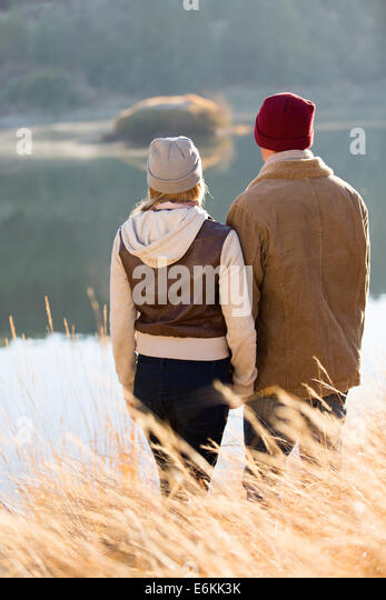 young couple standing by lake in autumn park - Stock-Bilder