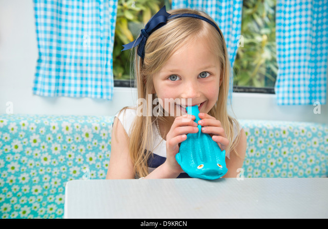 Portrait of young girl blowing up balloon in caravan - Stock Image