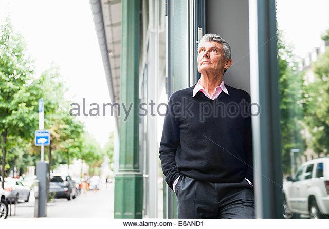 Sad senior man looking up from city street - Stock Image