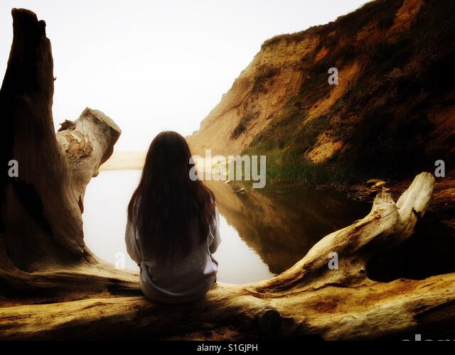 Girl sitting on log - Stock-Bilder