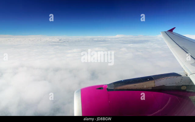 Part section of pink aeroplane fuselage flying above the clouds. belgium europe - Stock Image