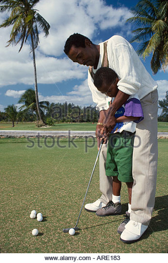 Bahamas New Providence Nassau Cable Beach Golf Course father teaching son how to play golf - Stock Image