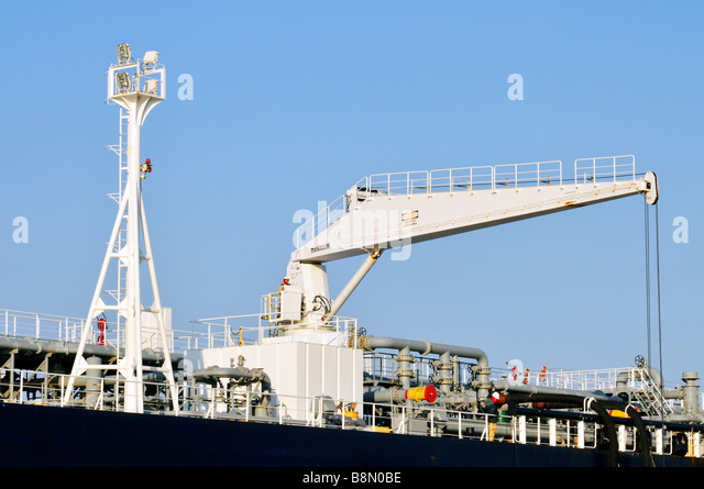 Deck of 'oil tanker' with crewmen operating a [hydraulic hose handling crane] showing tower mounted work - Stock Image