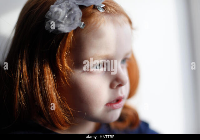 A 4 year old girl with ginger hair looking out of a window - Stock Image