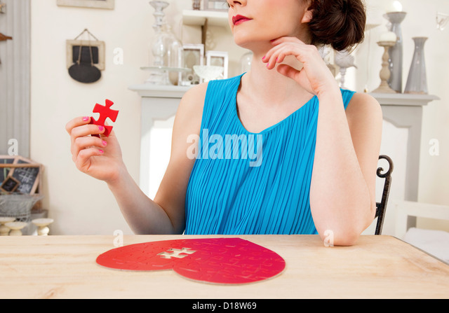 Woman doing heart shaped jigsaw puzzle holding piece - Stock Image