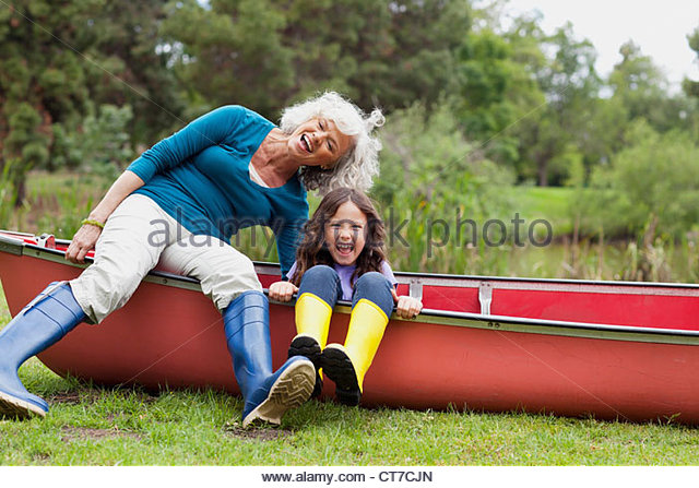 Grandmother and granddaughter sitting on canoe - Stock Image