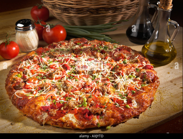 baked vegetable meat pizza with cheese sauce bred crust brown on wood cutting board next to oil basket tomatoes - Stock Image