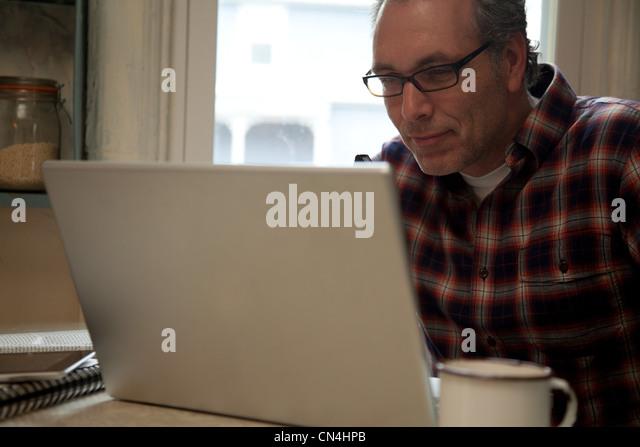 Mature man using laptop at home - Stock Image