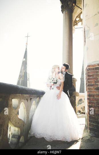 Kissing wedding couple staying over beautiful landscape - Stock Image