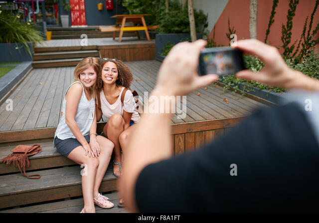 Two young woman sitting together posing for a photo being taking by their friend. Man taking photographs of his - Stock Image