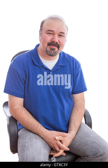 Close up Bearded Man in Blue Polo Shirt, Sitting on a Chair in an Optimistic Emotion and Looking at the Camera. - Stock Image