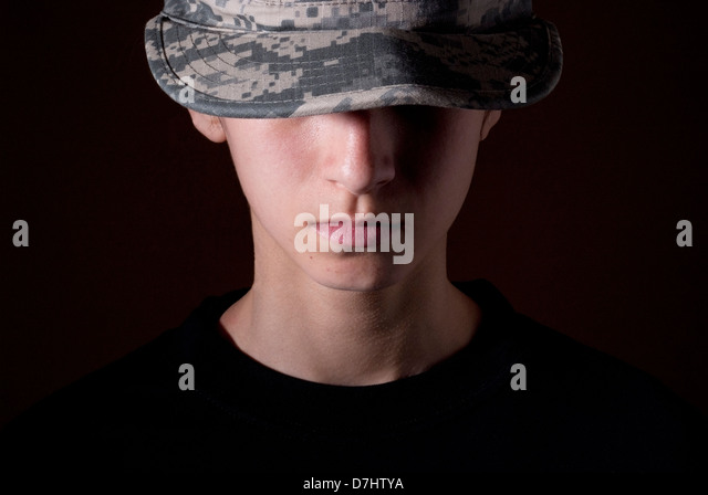 Young female wearing Woman's Army Combat (ACU) camouflage hat covering her face. - Stock Image