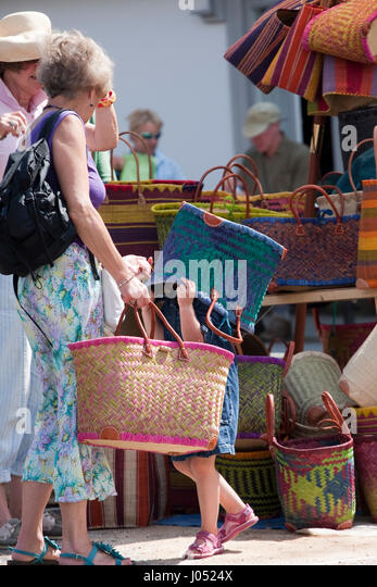 In a street market a small girl has put a shopping basket over her head - Stock Image