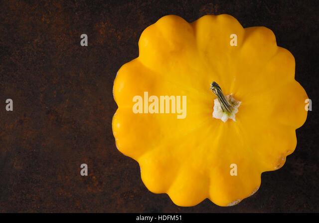 Yellow fresh pattypan squash on the rusty metal background horizontal - Stock Image