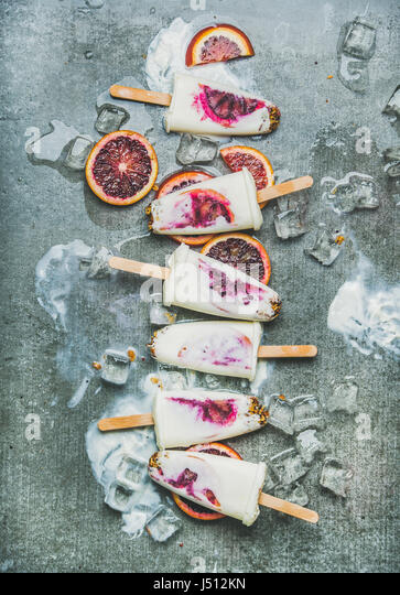 Healthy summer dessert. Blood orange, yogurt and granola popsicles on ice cubes over grey concrete background, top - Stock Image